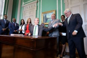 Mass Governor Charlie Backer sits at a desk with 7 people behind him, handing a pen to a man on the right